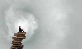 She is in dispair and isolation. Bored young businesswoman sitting alone on pile of books Stock Photo