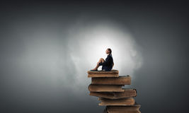 She is in dispair and isolation. Bored young businesswoman sitting alone on pile of books Royalty Free Stock Photos