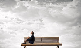 She is in dispair and isolation. Bored young businesswoman sitting alone on wooden bench Stock Photos
