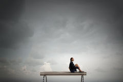 She is in dispair and isolation. Bored young businesswoman sitting alone on wooden bench Royalty Free Stock Photo