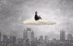 She is in dispair and isolation. Thoughtful young businesswoman sitting alone on cloud above city Royalty Free Stock Photo