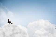 She is in dispair and isolation. Thoughtful young businesswoman sitting alone on cloud high in sky Royalty Free Stock Image