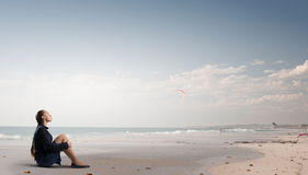 She is in dispair and isolation. Thoughtful young businesswoman sitting alone on ocean coast Stock Images
