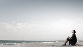 She is in dispair and isolation. Thoughtful young businesswoman sitting alone on ocean coast Royalty Free Stock Photo