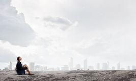 She is in dispair and isolation. Thoughtful young businesswoman sitting alone on rock top Stock Photos