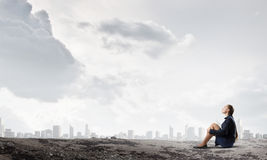 She is in dispair and isolation. Thoughtful young businesswoman sitting alone on rock top Royalty Free Stock Image