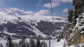 Disparado contra o movimento em um elevador de esqui da cadeira nas montanhas no inverno vídeos de arquivo