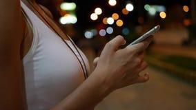 Disparado das mãos da mulher com o smartphone na cidade na noite Conceito da tecnologia filme