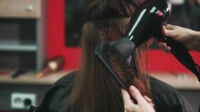 Disparado das mãos do ` s do cabeleireiro, que seca o cabelo com um secador e um pente de cabelo vídeos de arquivo