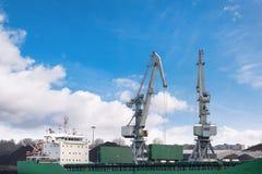 Disparado de dois velhos, o porto oxidado, cinzento cranes com os ganchos grandes, levantando a carga no navio no fundo claro do  foto de stock royalty free