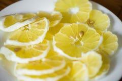 Disparado de fatias brilhantes, amarelas e ácidas do limão com as sementes na placa branca no meio da tabela Imagem de Stock