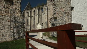 Disparado de um monastério velho com cerca e a monge de passeio vídeos de arquivo