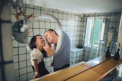 Disparado de uma ligação feliz dos pares ao escovar os dentes no bathr fotos de stock royalty free