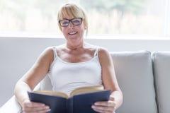 Disparado de uma mulher madura que lê sua novela favorita quando em casa na sala de visitas fotografia de stock