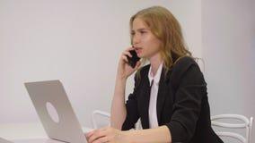 Disparado de uma mulher de negócios nova atrativa que trabalha no portátil em sua estação de trabalho filme