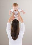 Disparado do bebê de levantamento da matriz loving acima da cabeça Foto de Stock Royalty Free