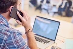 Disparado do homem que fala no telefone de trás o Imagem de Stock