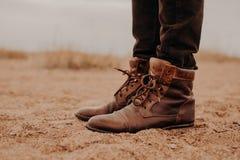 Disparado lateralmente do homem em sapatas marrons desgrenhados na superfície colocada Pares de botas na areia O homem tem a cami fotografia de stock