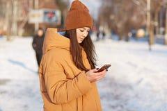 Disparado lateralmente do jovem fêmea vestido no chapéu à moda e no revestimento fraco, guarda o telefone celular, redes dos surf foto de stock