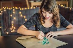 disparaissent le vert Le calligraphe Young Woman ?crit l'expression sur le livre blanc Inscrire les lettres d?cor?es ornementales photographie stock libre de droits