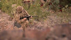 Disparando de cima de, o soldado no uniforme da camuflagem está guardando a arma automática e está estando na terra na menina da  filme