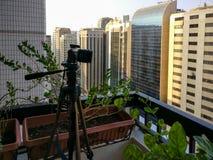 Disparando em um lapso de tempo do por do sol em um balcão na cidade - câmera e tripé imagens de stock royalty free