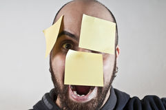 Disparate man with postit on his face. On white background Royalty Free Stock Photos