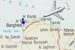 Dispare a Bengasi con el aeroplano del juguete y empuje el perno en mapa fotografía de archivo