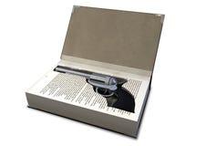Dispare contra encubierto en un libro imagen de archivo