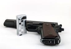 Dispare contra (potro 1911) y un encendedor en un fondo ligero Fotografía de archivo