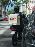 Dispatch Rider From GDExpress. Back view of the delivery man from the Malaysian courier company GDExpress GDEx on his motorbike, out on delivery Stock Image