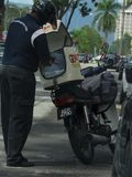 Dispatch Rider From GDExpress. Delivery man from the Malaysian courier company GDExpress GDEx, retrieving an item for delivery from his motorcycle`s delivery box Royalty Free Stock Images