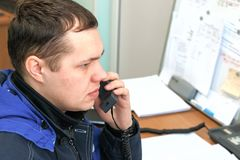 The dispatcher answers the phone and makes a decision. The dispatcher answers the phone. Young man in the workplace stock photography