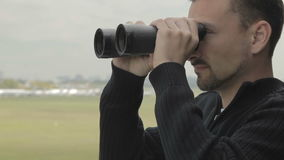 Dispatcher with binoculars controls air-traffic in the control tower. Outdoors in airport. Professional worker watches after planes with binoculars. Worker of stock footage