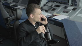 Dispatcher controls the air-traffic with binoculars in control tower in airport. Dispatcher controls the air-traffic with binoculars in the control tower in stock footage