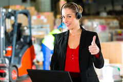Dispatcher using headset at warehouse of forwarding. Friendly Woman, dispatcher or supervisor using headset and laptop at warehouse of forwarding company Stock Images
