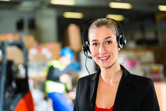 Dispatcher using headset at warehouse of forwarding. Friendly Woman, dispatcher or supervisor using headset at warehouse of forwarding company, smiling Stock Image