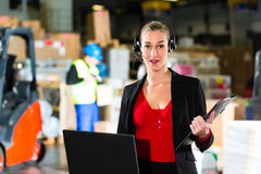 Dispatcher using headset at warehouse of forwarding. Friendly Woman, dispatcher or supervisor using headset and laptop at warehouse of forwarding company Stock Image