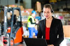 Dispatcher using headset at warehouse of forwarding. Friendly Woman, dispatcher or supervisor using headset and laptop at warehouse of forwarding company Royalty Free Stock Image