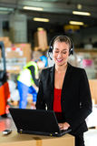 Dispatcher using headset at warehouse of forwarding. Friendly Woman, dispatcher or supervisor using headset and laptop at warehouse of forwarding company stock photos