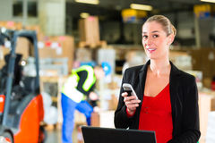 Dispatcher using phone at warehouse of forwarding. Friendly Woman, dispatcher or supervisor using cell phone and laptop at warehouse of forwarding company Stock Photography