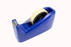 Dispensador azul de la cinta en el fondo blanco Fotografía de archivo