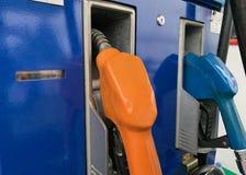 Dispensador del aceite que llena el aceite en la estación del aceite, anaranjado y azul fotos de archivo
