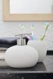 Dispensador del jabón con cepillos de dientes Imagenes de archivo