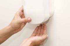Dispensador montado en la pared del desinfectante con la mano de la mujer imagenes de archivo