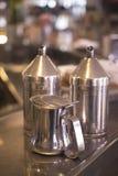 Dispensadores de la leche del azúcar del café en barra del café Foto de archivo
