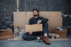 Disperato e senzatetto sta sedendosi sul cartone sulla terra e sta tenendo un pezzo di cartone Sembra stanco e Fotografie Stock Libere da Diritti