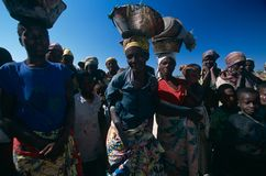 Displaced people in Angola. A large group of displaced people in Angola. Three of the people in the foreground are carrying pots in their head Royalty Free Stock Photography