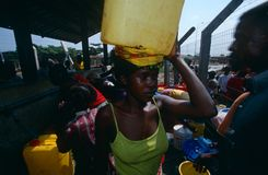 Displaced people collecting water in Angola. Displaced people collecting water at a camp in Angola. Woman carrying large water container on her head Royalty Free Stock Images