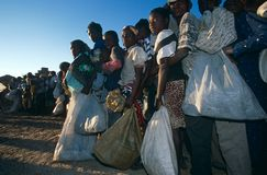 Displaced people receiving aid in a camp in Angola. Displaced people queue for receiving aid distribution by NGO CARE at a camp in Angola Stock Images